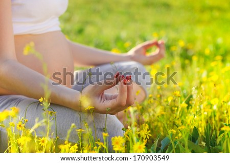 Healthy pregnant woman doing yoga in nature outdoors. Close up - stock photo