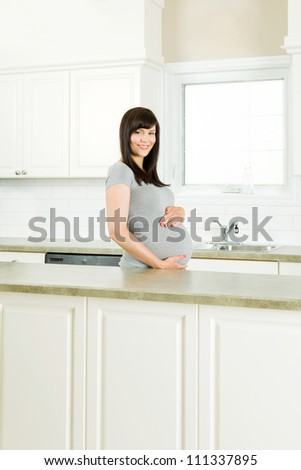 Healthy pregnant woman standing in kitchen behind counter