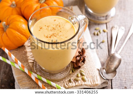 Healthy pumpkin smoothie in big mugs on rustic background - stock photo