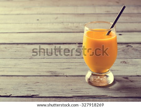 Healthy pumpkin smoothies with spices and nuts on rustic wooden table - stock photo
