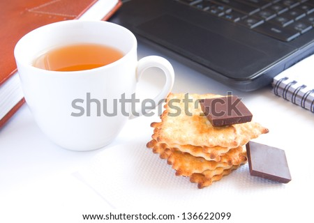 Healthy quick snack (lunch, break) in office. Cup of tea, cookies (biscuits) and chocolate on white desk with computer. - stock photo