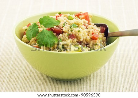 Healthy Quinoa salad in bright green bowl - stock photo