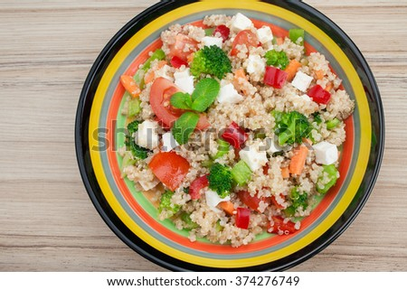 Healthy quinoa salad with mix of vegetables and white cheese. - stock photo