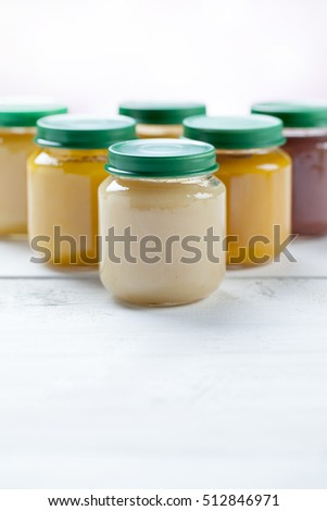 healthy ready-made baby food on a wooden table.