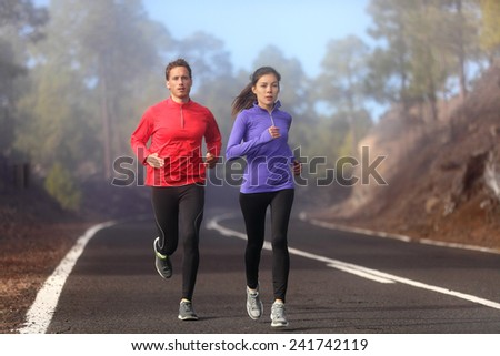 Healthy running runner man and woman workout on mountain road. Jogging male and female fitness model working out training for marathon on forest road in amazing nature landscape. Two runners - stock photo
