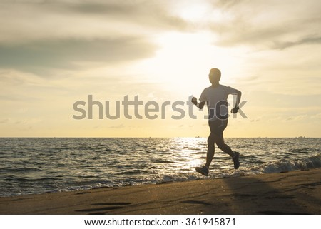 Healthy running runner man during sunset on the beach workout jog. sunflare through the mist gives atmospheric feel and depth to these fitness images