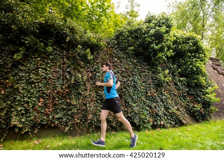Healthy running runner man  legs workout in a city park. Jogging male fitness model legs working out training  in a city park. - stock photo