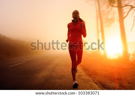 Healthy running runner woman early morning sunrise workout on misty mountain road workout jog. sunflare through the mist gives atmospheric feel and depth to these fitness images - stock photo