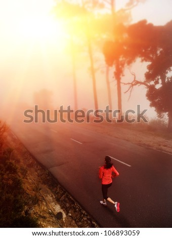 Healthy running runner woman early morning sunrise workout on misty mountain road workout jog. sun flare through the mist gives atmospheric feel and depth to this set of fitness images - stock photo
