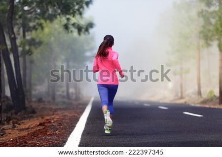 Healthy running runner woman workout on mountain road. Jogging female fitness girl working out training for marathon on forest road in amazing nature. - stock photo