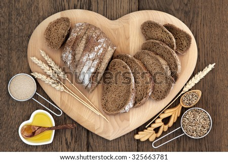 Healthy rye bread on a heart shaped board with wheat sheaths, yeast, oil, grain in love spoon and scoop over oak background. - stock photo