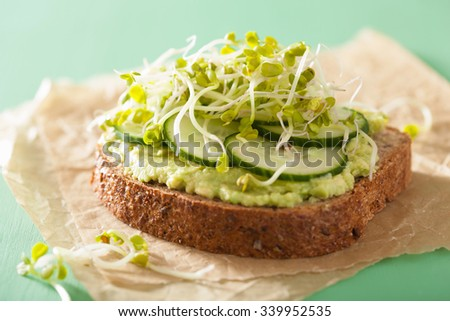 healthy rye bread with avocado cucumber radish sprouts - stock photo