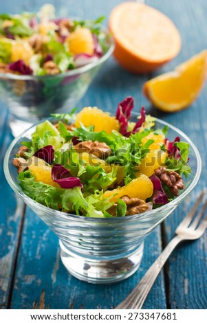 Healthy salad mix with orange and walnuts in glass on blue background, selective focus - stock photo