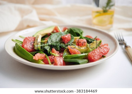 healthy salad with avocado, grapefruit and spinach. selective focus - stock photo