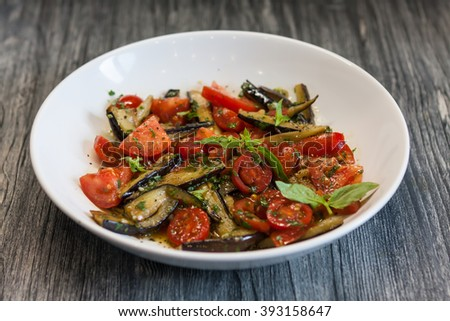 Healthy Salad With Cherry Tomatoes, Eggplant, Fresh Greens In White Plate  On Grey Wood