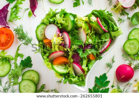 Healthy salad with fresh vegetables in heart shaped bowl and ingredients on white background, top view - stock photo