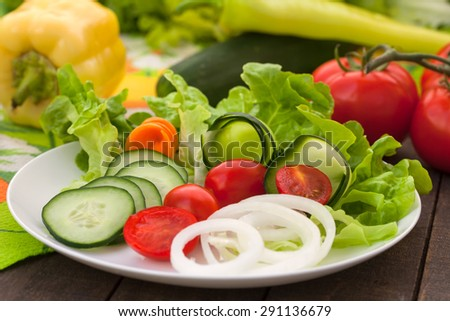 Healthy salad with lettuce, cucumber, cherry tomatoes and onions - stock photo