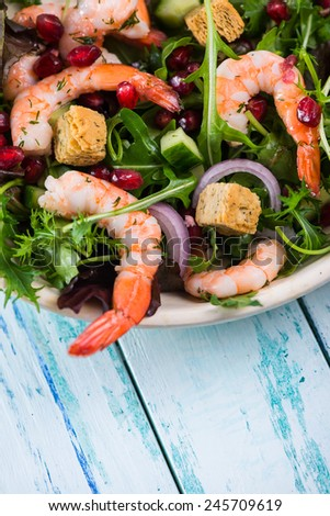 Healthy salad with seafood and pomegranate in rustic bowl