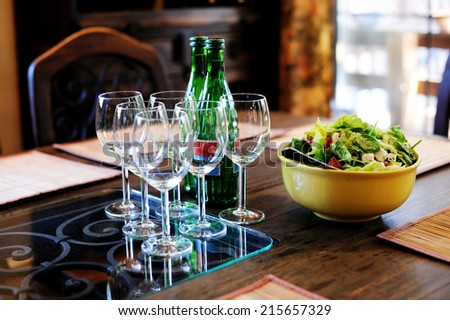 Healthy salads with lettuce, bell pepper, tomato and  cheese served with a glass of fresh water on a rustic wooden garden table