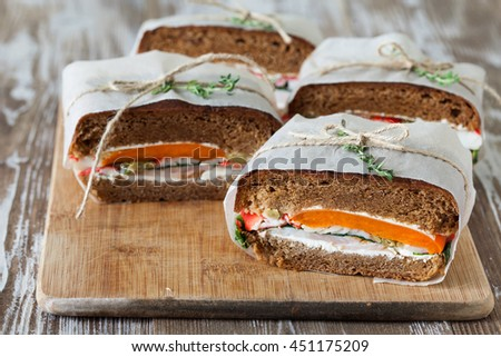 Healthy sandwich made of a fresh rye roll with tasty ingredients of ham, tomato, lettuce and arugula, presented on old wooden board - stock photo