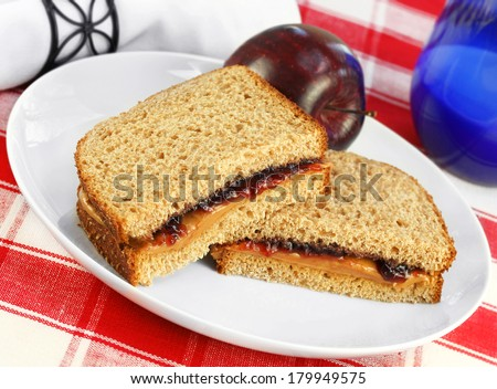 Healthy sandwich of peanut butter and grape jelly on whole wheat bread.  Fresh apple and a glass of milk complete the lunch. - stock photo