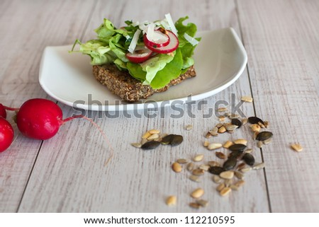 healthy sandwich with salad, radish and pumpkin seeds - stock photo