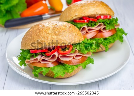 Healthy sandwiches with ham and a wooden board with vegetables on background - stock photo