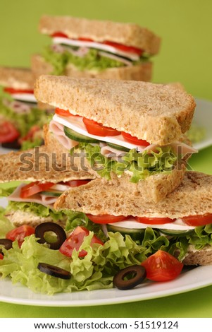 Healthy sandwiches with ham, camembert, tomatoes, cucumber, lettuce and black olives