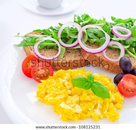 Healthy scrambled eggs breakfast with bread tomato arugula basil olives onions coffee - stock photo