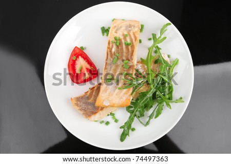 healthy sea food : roasted pink salmon fillet garnished with rucola, and tomatoes on white dish isolated over black background - stock photo