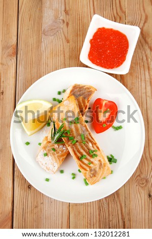healthy sea food : roasted pink salmon fillet on white dish with red caviar over wooden table