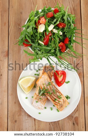 healthy sea food : roasted pink salmon fillet with vegetable salad on white dish over wooden table - stock photo