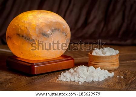 Healthy sea salt and salt lamp on wooden bowl closeup  - stock photo