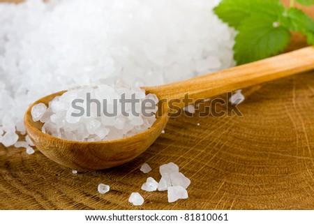 Healthy sea salt on wooden spoon closeup - stock photo