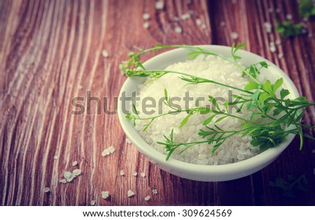 Healthy sea salt with herbs on wooden background - stock photo