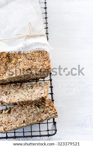 Healthy seeded multi grain whole wheat wholemeal loaf of bread with nuts, pumpkin, sunflower, sesame, flax seeds and almonds, plenty of copy space - stock photo