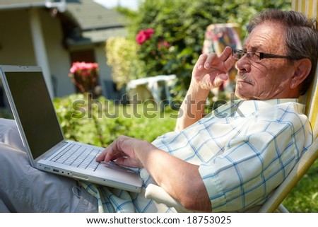 Healthy senior man is his elderly 70s sitting outdoor in garden at home and using laptop computer to browse internet. - stock photo