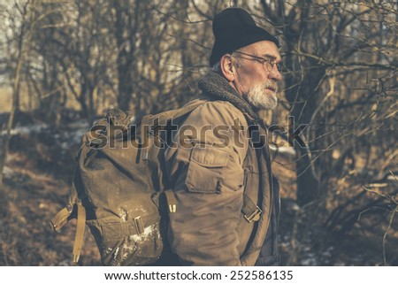 Healthy senior man with a beard and glasses wearing thick winter clothing and a knitted cap enjoying a wilderness hike with his backpack on his back, close up side view in woodland - stock photo