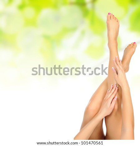 healthy sexy slender female legs being massaged over green natural spring background - spa and healthcare concept - stock photo