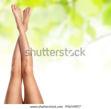 healthy sexy slender female legs over green natural spring background - spa and healthcare concept - stock photo