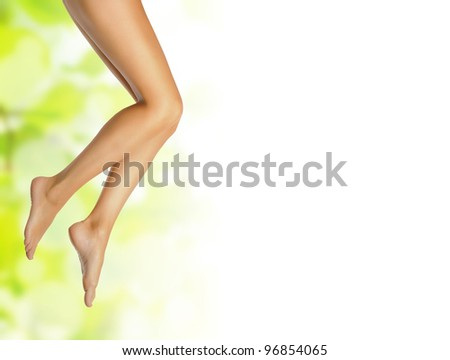 healthy sexy slender female legs over green natural spring background with white copyspace - spa and healthcare concept - stock photo