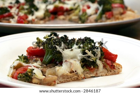 Healthy slice of vegetable pizza on whole wheat crust
