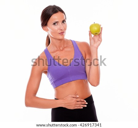 Healthy smiling brunette with apple looking at camera and a hand on her waist, wearing violet and black gymnastic clothing, her hair tied back, isolated - stock photo