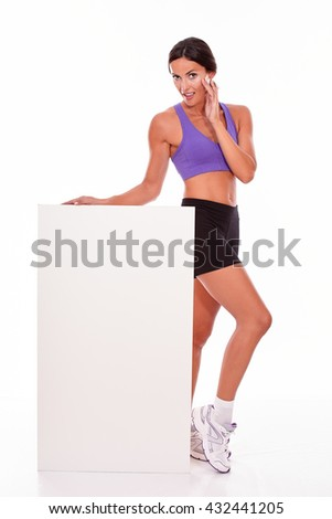 Healthy smiling brunette woman holding blank placard and looking at camera with one hand to her cheek while wearing violet and black gymnastic clothing, isolated
