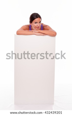 Healthy smiling brunette woman standing behind a blank placard and looking at camera resting her chin on hands while wearing violet gymnastic clothing isolated - stock photo