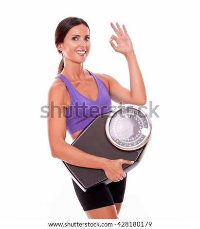 Healthy smiling brunette woman with a scale, gesturing a perfect sign while wearing her hair tied back and violet and black gymnastic clothing, isolated - stock photo