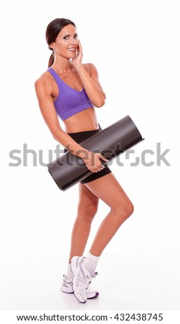Healthy smiling brunette woman with a yoga mat looking at camera with one hand to her cheek while wearing violet and black gymnastic clothing isolated - stock photo