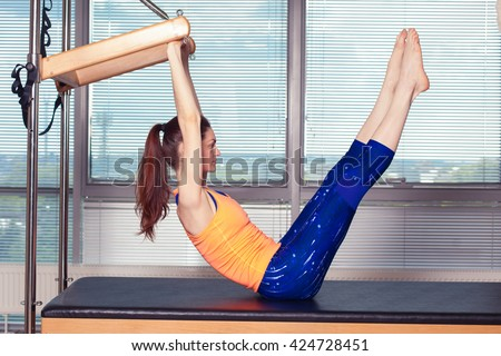 Healthy Smiling Woman Wearing Leotard Practicing Pilates in Bright Exercise Studio - stock photo