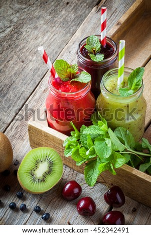 Healthy smoothie from kiwi, raspberries and blueberries in a jars with straws and mint leaves in wooden box on old table with copy space. - stock photo