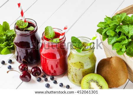 Healthy smoothie from summer fruits and berries in a jars with straws - stock photo